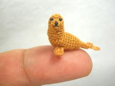 Micro crocheted tiny fin-footed mammal - Brown seal.  The little seal is made embroidery threads, sewn plastic eyes cored and stuffed polyfil.  Size: Measure approx. 0.8 inch ( 20mm) long.  Perfect for any DOLLHOUSE, would be a lovely gift for the seal lovers or MINIATURE of your mini animal