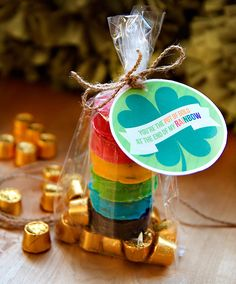"St. Pat's Rainbow Cookie Treat: ""Melt white chocolate, and add food coloring or pre-colored Wilton Candy Melts, one melted chocolate for each color of the rainbow.  Dip your favorite sandwich cookies and allow to set. Fill the bottom of a bag with individually wrapped Rolo candies or any gold wrapped candy, and stack your rainbow cookies on top. Twist the bag closed and tie on our printable tag."""