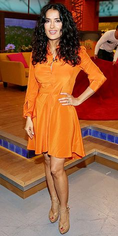 Salma Hayek Brightens Up Univision Studios in an Orange Alexander McQueen Dress - theFashionSpot -- I adore Salma. She looks gorgeous here. Has inspired me to stop medicating myself with chocolate and fix myself up so I can look almost as fabulous. Estilo Salma Hayek, Salma Hayek Style, Salma Hayek Pictures, Selma Hayek, Studios, Alexander Mcqueen Dresses, Orange Dress, Petite Fashion, Beautiful Actresses