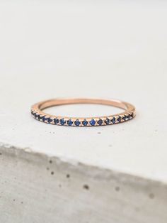 This ring is a gorgeous micro-pave eternity ring. This eternity band is ultra thin and has sapphire stones covering half of the band. Looks great on on its own or stacked! Rose Gold Plated brass with