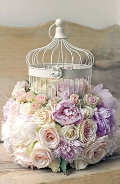 Stunning idea for a table centre-piece or decoration of a surface, mantle-piece or table. Vintage bird-cage filled with loose roses.