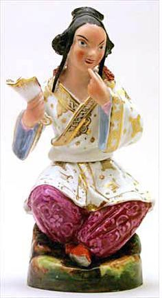 """Teapot #453  Figurine, seated """"Chinese Lady"""" wearing white and gold short kimono over magenta pantaloons,   a matching ornament decorates black coiffure; fan in right hand forms the spout. Companion to   No. 452."""