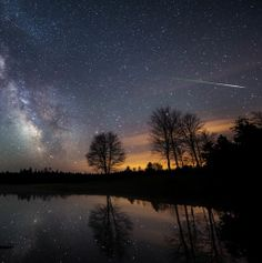 "An eta Aquarid fireball meteor streaks through the pre-dawn sky in central Maine sky 2014-05-06. (Credit: Mike Taylor) The Milky Way is reflected in a pond. Beautiful shot. Mona Evans, ""Meteor Shower - the Perseids"" http://www.bellaonline.com/articles/art27461"