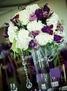 Set on gold table linens were tall centerpieces of white hydrangeas mixed with purple flowers and gold toned roses, and ivy, as well as hanging crystals and candles. Description from pinterest.com. I searched for this on bing.com/images
