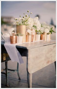 regular old tin cans spray painted in metallic colors and filled with flower