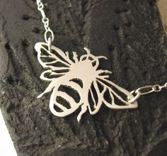 Honey-bearing bee is intricately cut from a sheet of sterling silver. Ive included some of the fine details in the wings as well as cuts to show fuzziness in the body of this little garden friend.  She is 1 1/4 from wing tips and 3/4 high. A sterling silver chain is attached to each wing. (*delicate sterling silver chain will be used and will vary slightly from the chain pictured). Every piece of jewelry is handcrafted by me and as a result, each piece is unique and may have slight…