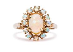 The vintage Opal Halo Ring is brand new to the Trumpet & Horn collection. Featuring a white oval opal in a halo of smaller opals, this cheery and fun ring could be a unique, colorful engagement ring, or an unforgettable right hand ring. Love!   $700 themarriedapp.com hearted <3