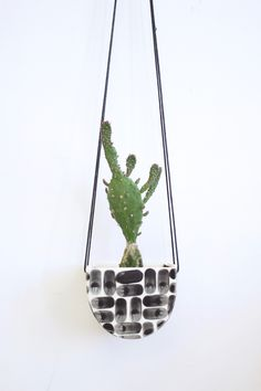 Handmade by potter Elizabeth Benotti in New Hampshire, this half moon shaped hanging planter can be hung in a window or flush against the wall. Hang multiple together for a pop of plant life in any ro