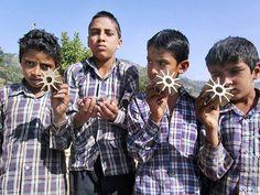 Young boys show parts of a mortar shells