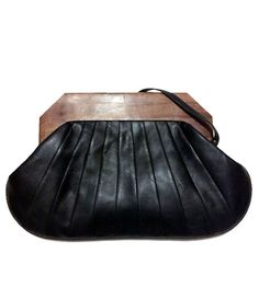 Over-sized clutch features a folded leather exterior  held in placee by a chunky wood handle. Gorgeous.