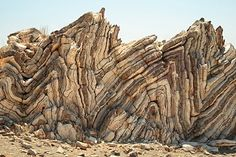 These rock layers started out flat and have been compressed into accordion shapes by regional pressures.
