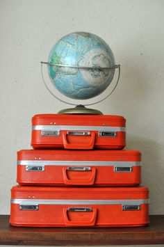 Three pieces of electric-orange vinyl hardside luggage. A larger case, a carry-on size case, and a vanity case