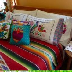Painted headboard and embroidered pillows for a colorful Mexican embroidered bedding