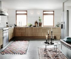 I love this beautiful homes with the concrete floors. The wood from the kitchen cabinets matches just perfectly with the white tiles and floors and I like the brown tints in the windows and of the cor