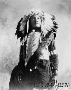Striking photo of a Sioux Native American in full feather headdress and bone breast plate