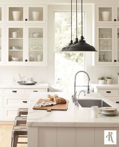 white kitchen with pretty details: glass cabinets, pendant lights, marble counters, metal stools