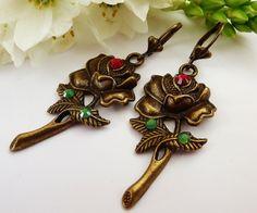 Diese romantischen Ohrringe bestehen aus bronzefarbenem Metall und sind mit hochwertigem Strass in rot und opalgrün verziert.  Der Ohrschmuck ist nick