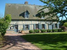 Une belle maison normande, aux colombages et aux volets peints en bleu-gris.