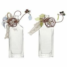 "Add a lovely touch to your entryway console table or living room mantel with this whimsical glass bottle, showcasing a wire and lace accent.   Product: Set of 2 bottlesConstruction Material: GlassColor: Clear and multiDimensions: 4.75"" H x 1.5"" W x 1"" D"