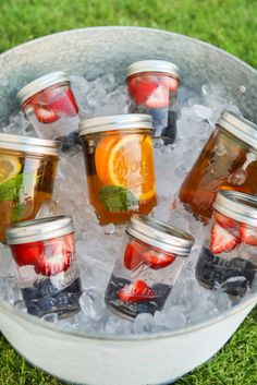 Fruit infused waters ready to go in mason jars make colorful beverage choices for wedding and event guests.