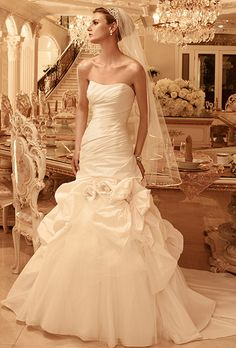 Brides: Casablanca Bridal. Ruched Crystal Tafetta gown with a soft sweetheart neckline. Gown has pick-up skirt accented with beaded rosettes and bow. A pick-up layer of tulle peeks out from the rosettes and bow detail on front skirt. Buttons and loop closure down the length of the zipper. This gown features an inside hook and eye fit panel.