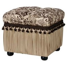 "Tufted ottoman with a ruched base and tassel trim.  Product: OttomanConstruction Material: Wood and fabricColor: Brown and creamFeatures: Button tufted topDimensions: 19"" H x 18"" W x 18"" D"