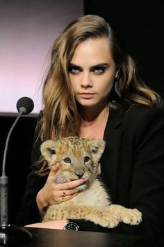 Cara Delevingne cuddles with a lion cub at the Tag Heuer 2015 Campaign launch in Paris