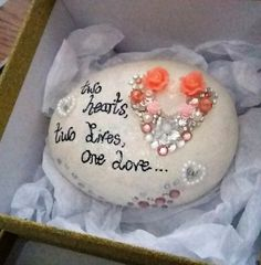This hand painted stone would make a adorable gift as wedding shower present. Or a wedding day gift to give as a token, it can be given in place of a card and will last for years. Original cream acrylic painted stone. With clear sparkly paint over the top. Hand written the words Two hearts, Two lives, One love.  Hand decorated with sparkly flowers,hearts and gems to form a bigger heart.  The size of stone is 6cm x 5cm. Weighs 200g. It comes in a gift-box ready for giving.  The stone is…