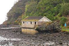 Little Huia. August 2010. This ageing boat house watches over the outgoing tide on a grey and misty morning. It is located at the end of Huia Rd, where Whatipu Rd leaves the coast to cross the ranges. The hill rising behind the building is Te Komoki (Jackies Peak). Nz History, Boat House, Ageing, Auckland, How To Be Outgoing, Ranges, Kiwi, New Zealand, Coast