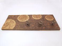 Perchero con diferentes estelas tallado en madera de roble en altorrelieve, tratado con betún judaico a dos tonos con tres perchas de hierro artesanales.  Dimensiones: 60×25cm.aprox.