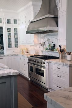 Kitchen/ marble niche behind stove with pot filler.  Unique SS hood.  Huge crown atop cabinets.  Thick marble counter tops.  Glass cab doors with counter top drawer.