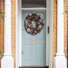 The pretty soft grey blue of this door is offset by the orange tones of the brick and the natural, silvery Christmas wreath.