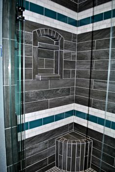 Check out the bench and niche in this shower with vertical planks that serve as a focal point! The eye is drawn to these 2!