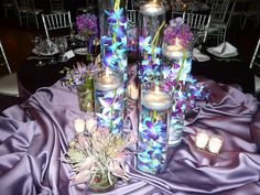 Purple flower centrepieces with floating candles....would do a white/off-white tablecloth