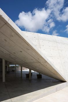 The folded concrete canopy of this burial service structure in an Israeli graveyard is supported by slender tree-shaped columns that pay homage to a razed orchard.