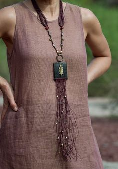 Necklace | Amalthee Creations.  Ethnic beads on waxed cotton threads enlighten a dark polished leather square ornate with a Baule bead