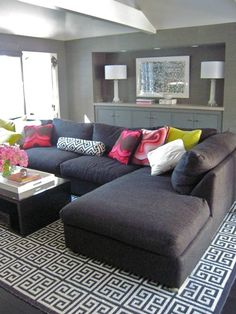 patterned rug, dark couch, bright pillows