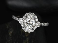 This engagement ring is designed for those who love simple with a slight twist. With the combination of both the 3 stone and halo together, the ring