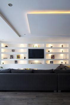 Living room | open plan seating | feature built in wall shelving | large corner sofa | lounge | modern mood lighting | interior design | built in TV | Brighton Architects