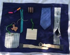 This masculine fidget quilt is great for the Autistic, & Alzheimers and Dementia patients hand and mind therapy. Great gift to a loved one in a nursing home or rehabilitation center. Features include a working belt buckle, zipper, soft beads on a ribbon, a keychain to put in pocket, buttons. Perfect for laps or a table. Please spot clean or hand wash and dry flat. As is, ready to ship.