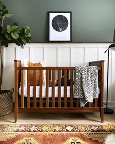 Gorgeous green walls in nursery with brown crib and white wainscotting