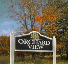 """Everyone wants to feel good when they arrive home. The """"Orchard View"""" composite subdivision entrance sign sent out a highly visible yet endearing message to everyone. This subdivision sign featured a rich blue background that displayed the town's signature logo in striking white paint. The shimmering metallic gold paint in the deeply carved tree design further enhanced the understated elegance of this simple, yet effective subdivision sign. #signage #subdivision #signs"""
