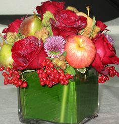 This is a cube vase floral arrangement that features roses and apples in a red and green color scheme.  See our entire selection at www.starflor.com.  To purchase any of our floral selections, as gifts or décor, please call us at 800.520.8999 or visit our e-commerce portal at www.Starbrightnyc.com. This composition of flowers is generally available for same day delivery in New York City (NYC). SQ044