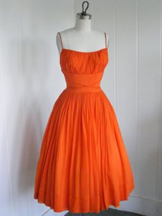 Bright hot orange, little spaghetti straps, ruched bustline, cinched waist, barely dropped gathered skirt. Tea length.
