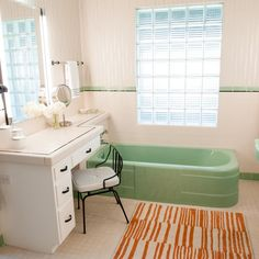 This adorable midcentury modern bathroom is filled with fun vintage accents and pops of color. An antique telephone ties in neatly with the black and white dressing table. And just try not to smile at the mint green bathtub and sink.