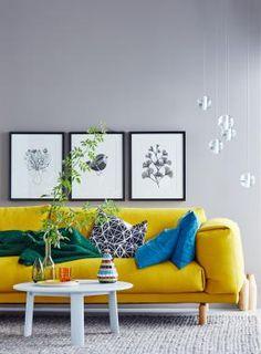 Sofa in Gelb vor Wand in Grau