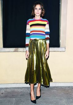Alexa Chung wears a rainbow stripe Gucci sweater, gold pleated midi skirt, and black pumps
