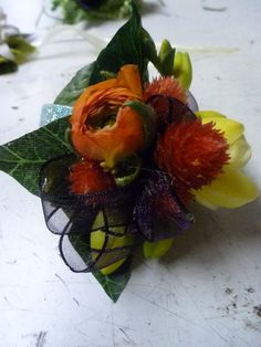 This corsage is a funktastic! The visual harshness of the thistle texture against the soft silkiness of the orange Ranunculus is visually interesting.  Love it!