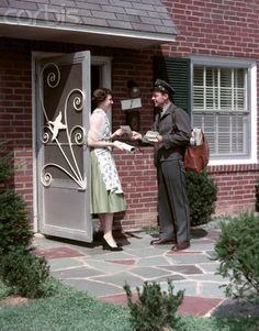 The friendly mailman.....love this photo! That aluminum storm door, housewife wearing an apron over her everyday wear and a mailman in a proper uniform with hat.