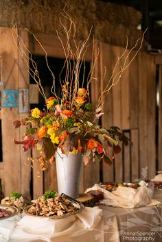 Anna and Spencer Photography, Atlanta Documentary Wedding Photographers. Fall Floral and Leafy Centerpiece on a Buffet Table at a Barn Wedding Reception. Flowers by Making Arrangements of Chattanooga, TN.